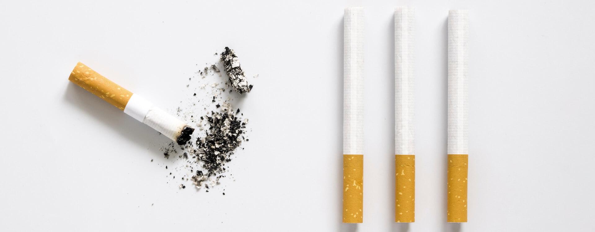 Cigarety - vyfajčený nedopalok cigarety a popol, cigarety rozložené na bielom pozadí